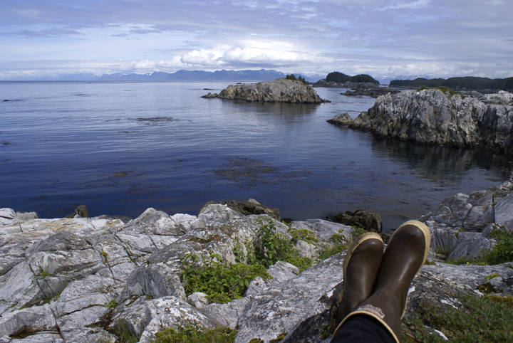 The photographer's boots rest on a rocky cliff line, as he looks out across the cool blue waters of the ocean to a far off blue shaded shore.